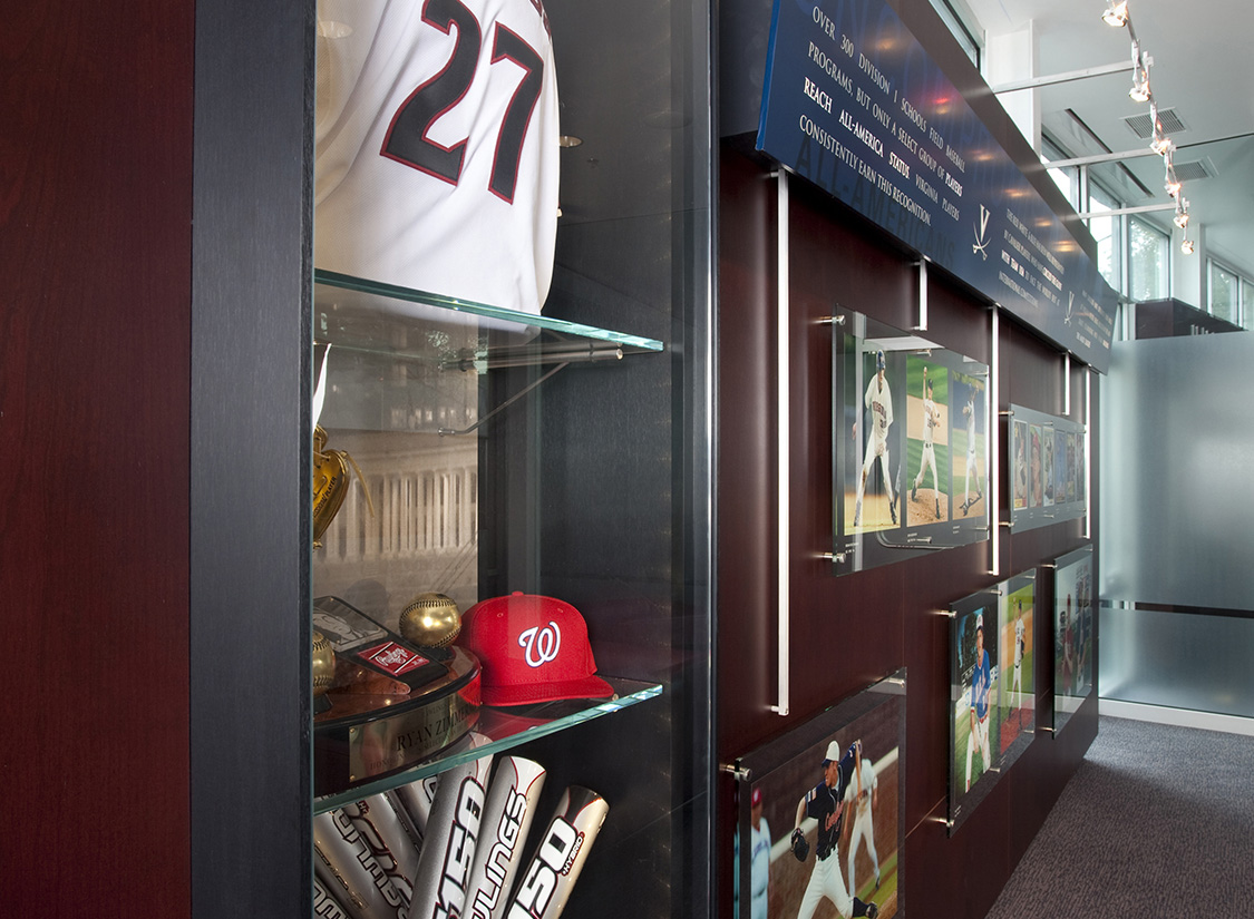 The opposite wall holds a mixed media exhibit of display cases. Glass cases hold the program's most prestigious championship trophies and player artifacts along with recognition of those players who have made it to the MLB. This room physically distills the success of the program over time and inspires incoming players to consider what their future might hold at UVA as well.