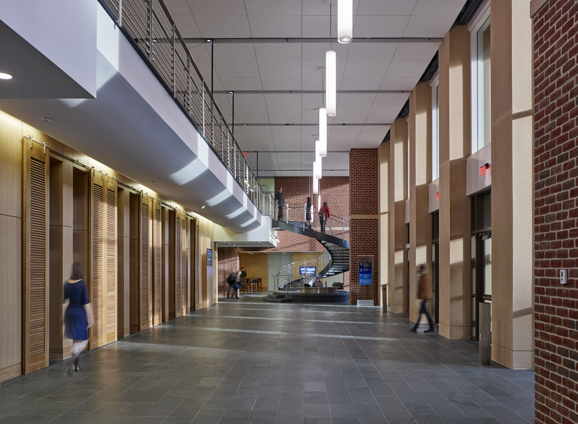 A generous multi-level promenade stitches together the main building's public spaces and academic programs.