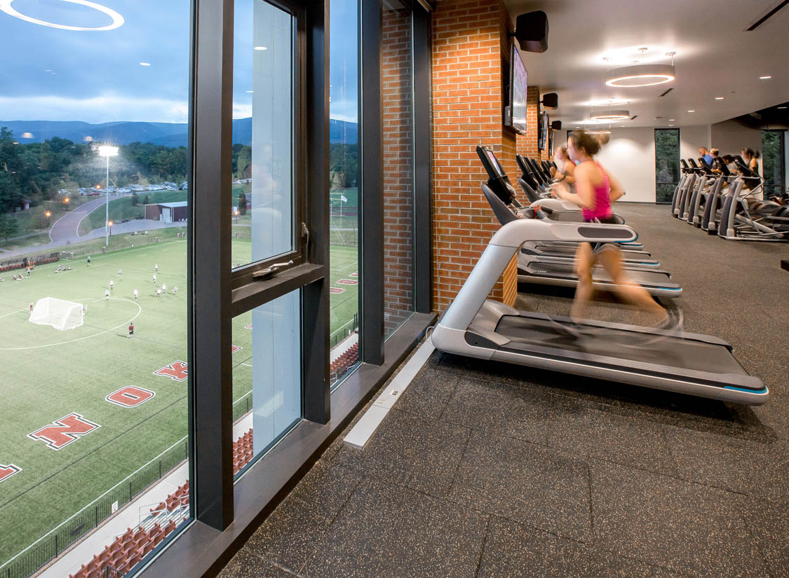 The Cregger Center houses three main volumes: a 2,500-seat basketball arena and performance gym (with 12 locker rooms), a field house with a 200-meter indoor track, and a fitness center open to the community and overlooking Kerr Stadium and the Blue Ridge Mountains.
