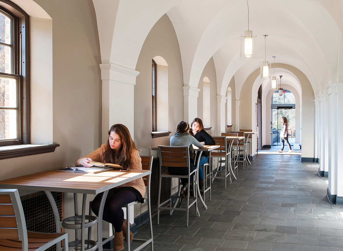 A vaulted gallery along the front of the entry façade has been reopened as a 24-hour study area with student art adorning the arcade's niches.