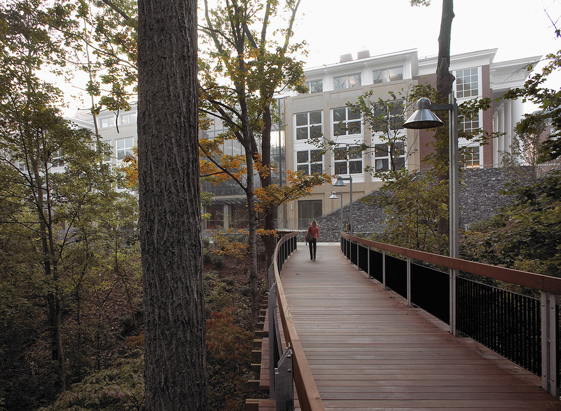 Instead, the design submerges service, reclaiming these areas as outdoor green spaces, and restores a 1920's master plan to treat the wooded creek as a park.